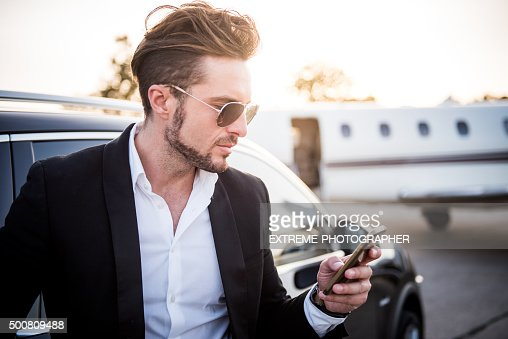 Man on the airport holding mobile phone : Stock Photo