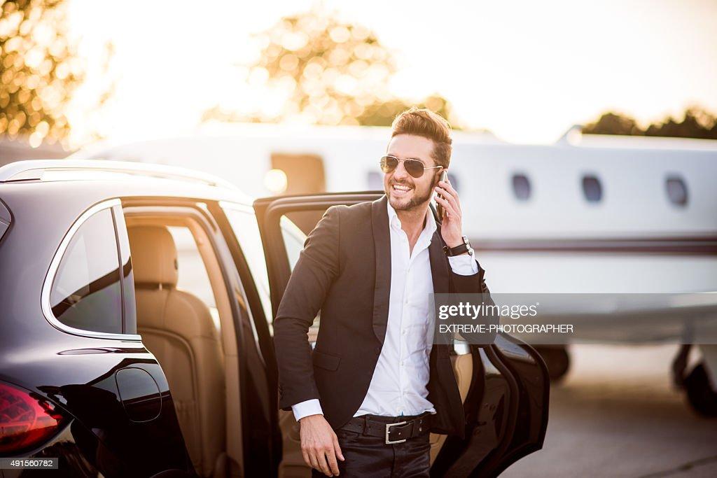 Mann auf dem Flughafen mit Telefon in der hand : Stock-Foto
