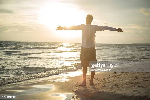Man on the beach opens arms to sunset