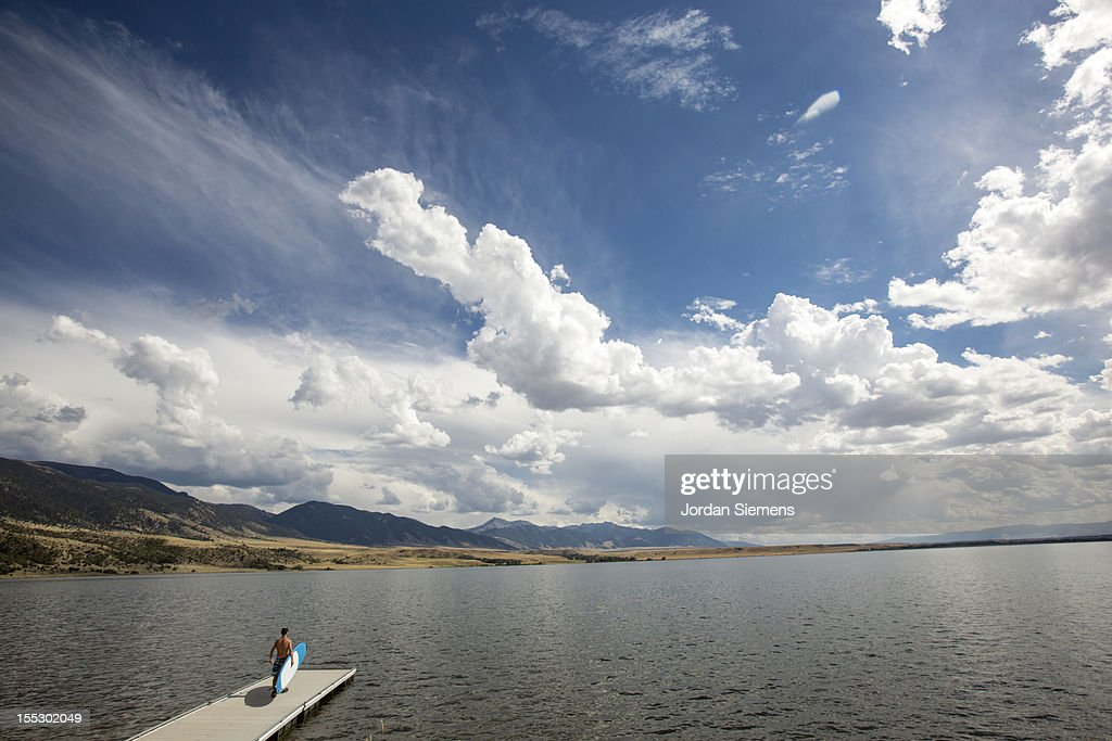 A man on the end of a dock looking at big clouds. : Stock Photo