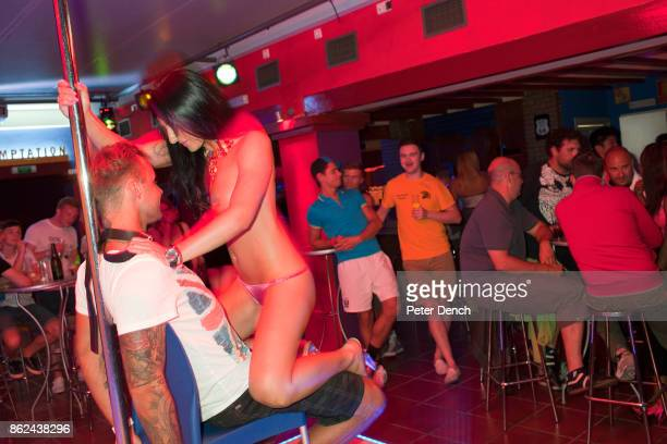 A man on the Invasion Ibiza bar crawl receives a lap dance from a woman working at the Temptation Bar in the West End area of San Antonio