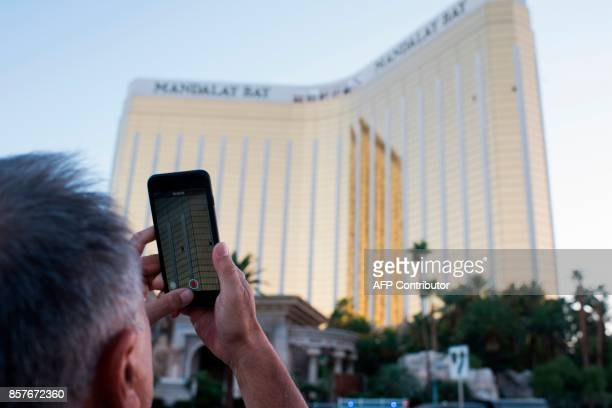 A man on the Las Vegas Strip October 4 films on his phone the two broken window in the Mandalay Bay hotel from which killer Stephen Paddock let loose...