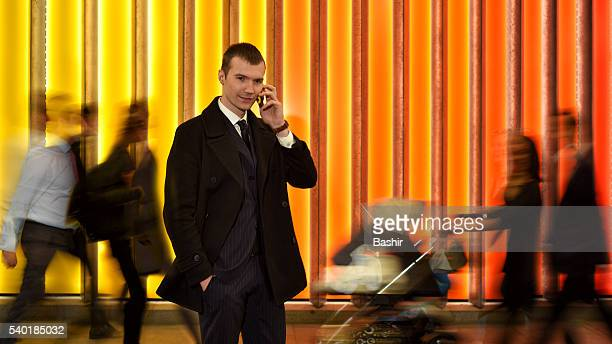man on the phone amongst city crowds
