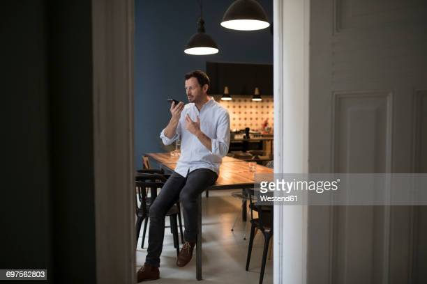 Man on the phone sitting on table in his kitchen