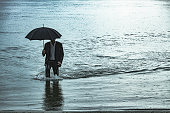 Adult man wearing full suit and holding umbrella and briefcase, comes out of the water near the river bank, during rainy day. The shot is executed with available natural light, and the copy space has