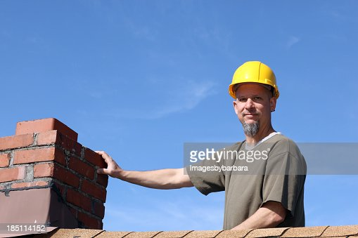 Man on the roof with hard hat performing a chimney sweep