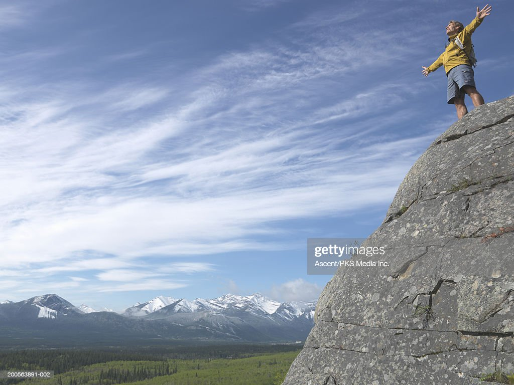 Man on top of mountain with arms outstretched, low angle view : Stock Photo
