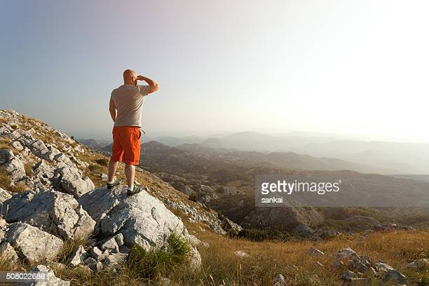 Man on top of the mountain looking ahead