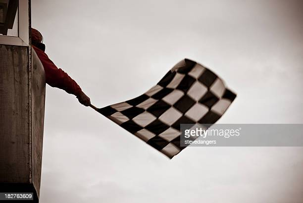 Man on tower waving checkered flag