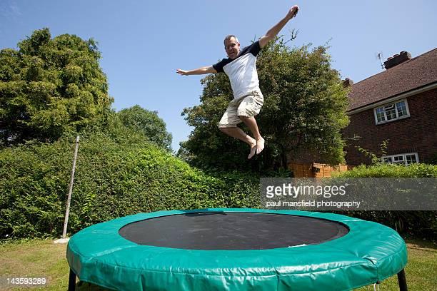 Man on trampoline in garden