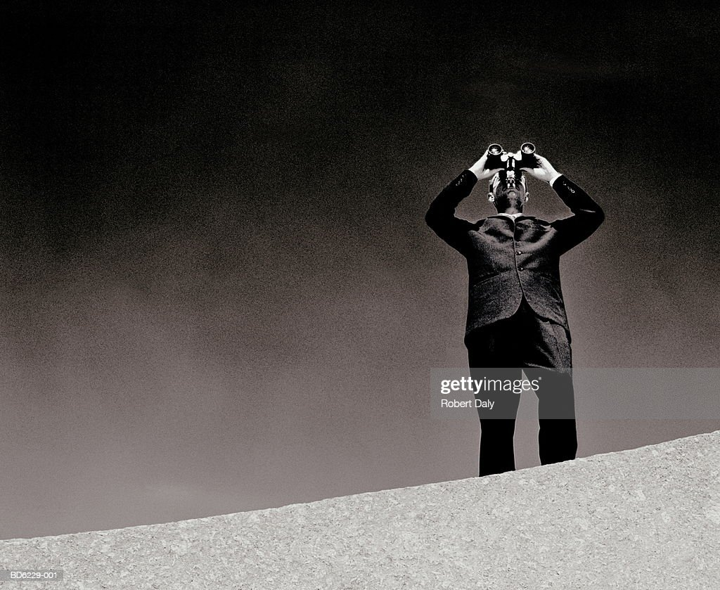 Man on wall using binoculars (B&W) : Stock Photo