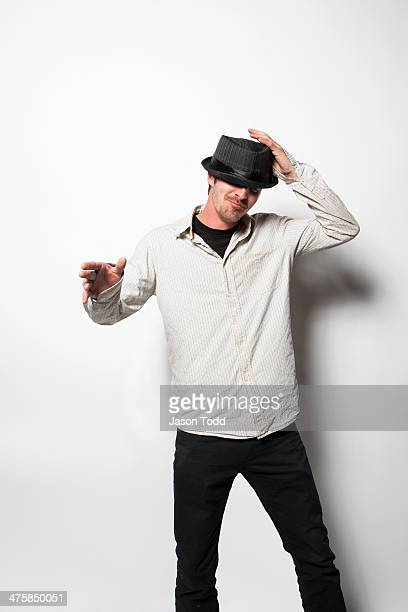 man on white tipping hat and dancing
