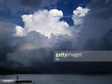 Man on wooden raft under stormy clouds