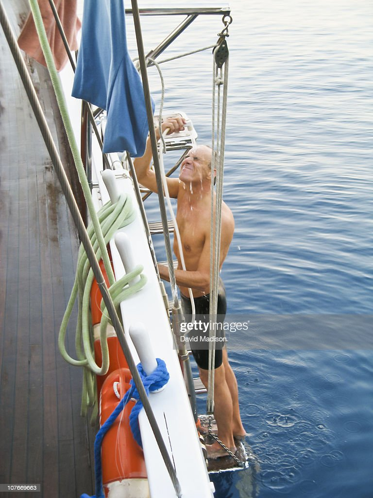 Man on yacht ladder showering after swimming. : Stock Photo
