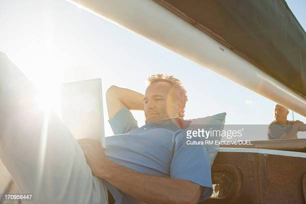 Man on yacht with digital tablet