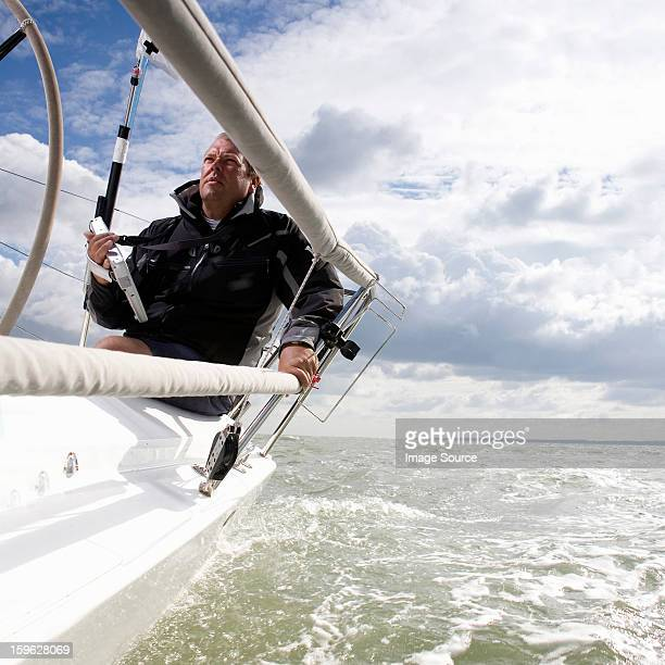 Man on yacht, with navigation aid