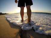 A man on Yallingup Beach Western Australia. Low view of feet and legs. Gopro image.