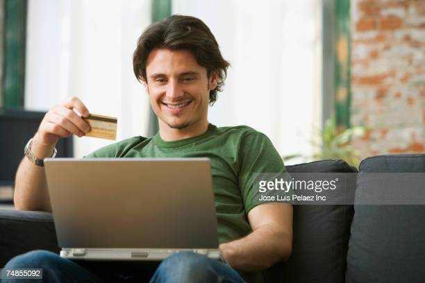 Man online shopping on sofa