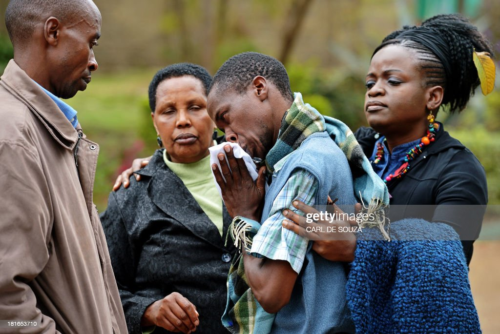 A man only identified by his first name, Stephen (C) is comforted by Pastor Elizabeth Akinyi (R) and family members at the city mortuary in Nairobi on September 23, 2013. Stephen's father was killed in the Westgate mall siege on September 21, 2013. Kenyan Defence troops remain inside the mall, in a standoff with Somali militants after they laid siege to the shopping centre shooting and throwing grenades as they entered. AFP PHOTO/Carl de Souza