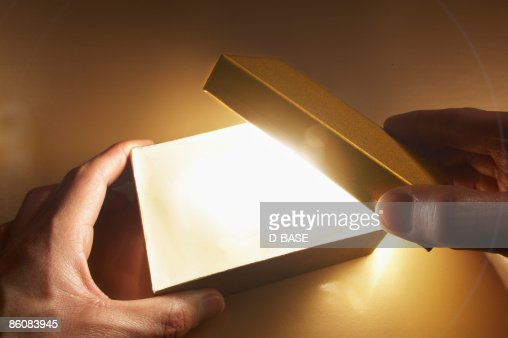 man opening a box with light coming out. : Stock Photo
