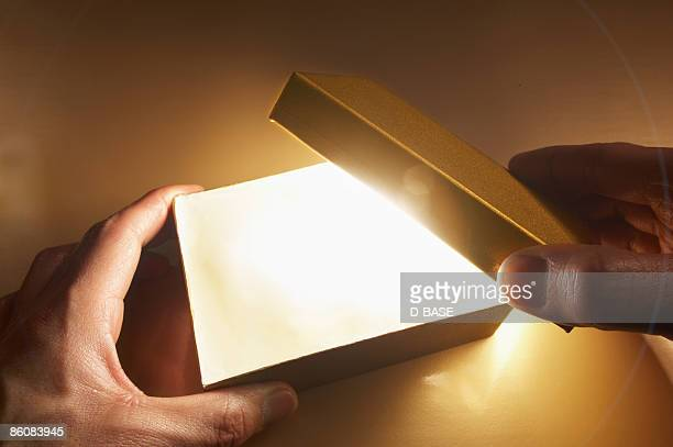 man opening a box with light coming out.