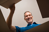 Happy mature man looking into parcel cardboard box and smiling. Cheerful senior man happy on seeing package. Smiling man feeling overjoyed on seeing parcel and opening it.