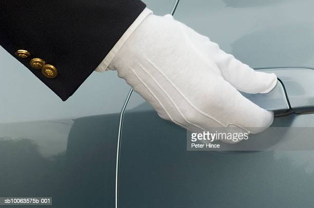 Man opening car door, close-up of gloved hand