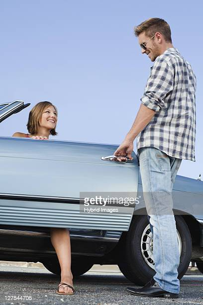 Man opening car door for girlfriend