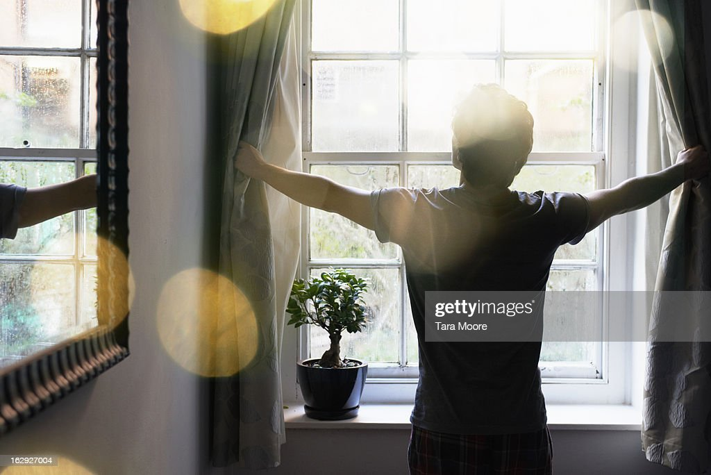 man opening curtains in the morning : Stock Photo