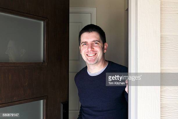 Man opening door at entryway to house