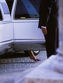 Man opening door of limousine for woman, low section