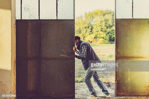 man opening doors of agricultural shed