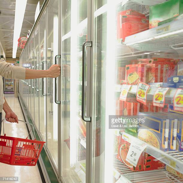 Man opening freezer door at supermarket