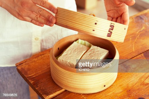 Man opening lid of steamer containing tofu, mid section : Stock Photo