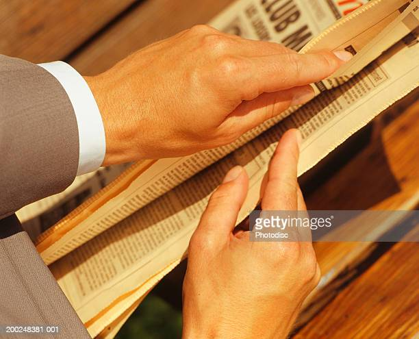 Man opening newspaper, Close-up of hands