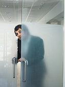 Man opening transparent door from behind