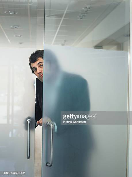 Man opening transparent door from behind