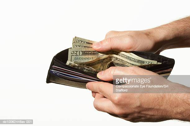 Man opening wallet full of American currency, close-up of hands