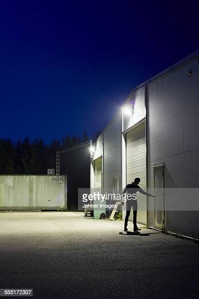 Man opening warehouse back door at night