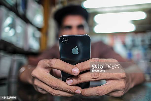A man operates a Apple Inc iPhone at a mobile phone store in this arranged photograph in Mumbai India on Saturday Feb 28 2015 The government auction...