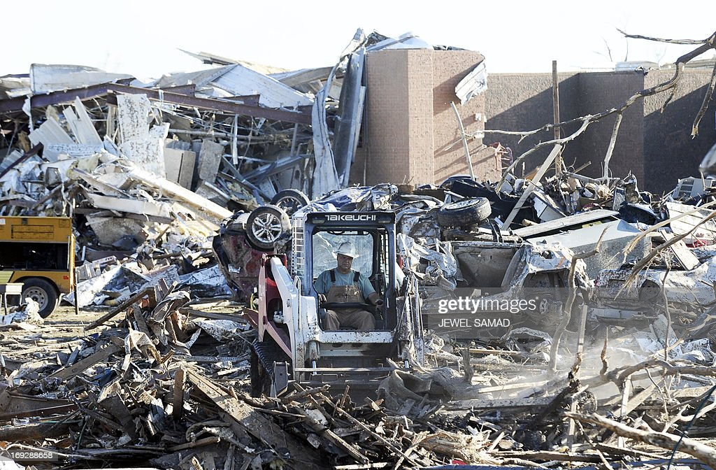 A man operates a bulldozer to clean debris from the front of tornado devastated Plaza Towers Elementary School on May 22, 2013 in Moore, Oklahoma. Seven children died in the school during the tornado. As rescue efforts in Oklahoma wound down, residents turned to the daunting task of rebuilding a US heartland community shattered by a vast tornado that killed at least 24 people. The epic twister, two miles (three kilometers) across, flattened block after block of homes as it struck mid-afternoon on May 20, hurling cars through the air, downing power lines and setting off localized fires in a 45-minute rampage. AFP PHOTO/Jewel Samad