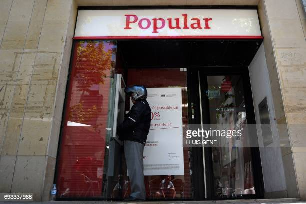 A man operates at the ATM at a Banco Popular branch on June 7 2017 in Vilanova i la Geltru near Barcelona after European authorities announced the...