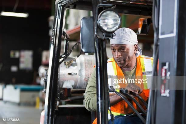 Man operating forklift in carpet warehouse