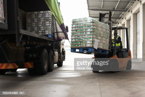 Man operating forklift truck loading pallets onto lorry