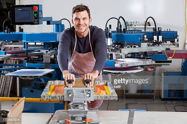 Man operating screen printing equipment