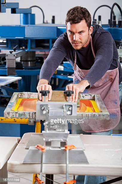 Man operating screen printing equipment