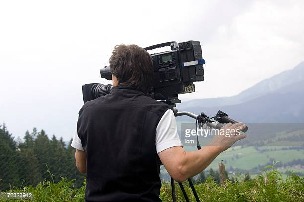 Man operating video camera in mountains