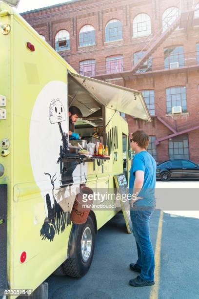 Man ordering food in a food truck in city street.