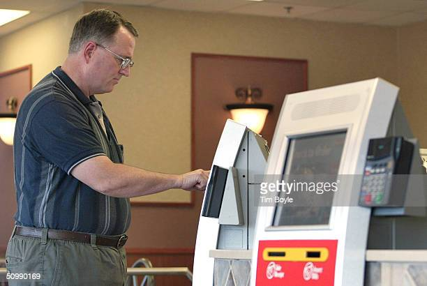 A man orders a meal from a computerized kiosk inside a McDonald's restaurant June 23 2004 in St Charles Illinois McDonalds has introduced the kiosks...