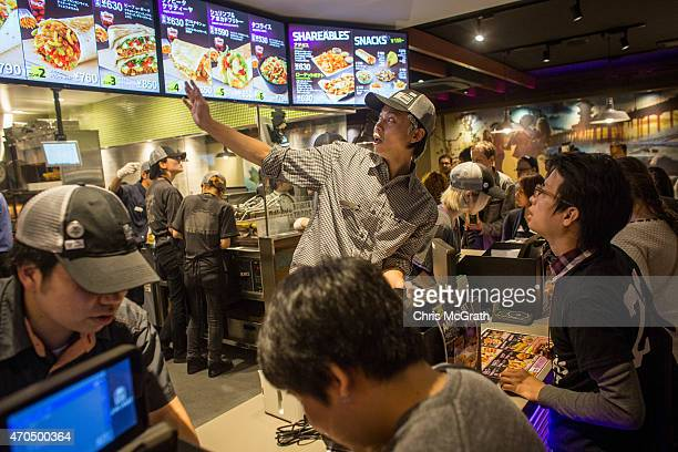 A man orders food inside the new Taco Bell store during the official opening on April 21 2015 in Tokyo Japan The new store operated by Asrapport...